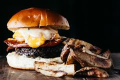 L'hamburger surdimensionato con chorizo e un uovo fritto è servito con il francese fotografie stock libere da diritti