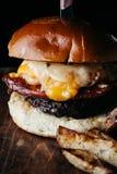 L'hamburger surdimensionato con chorizo e un uovo fritto è servito con il francese fotografia stock