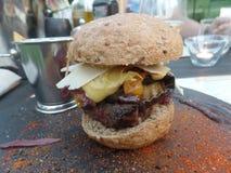 L'hamburger in un panino integrale è servito con le fritture fotografie stock libere da diritti
