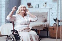L'handicap allegro ha invecchiato la donna che parla sullo Smart Phone a casa fotografia stock
