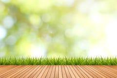 L'herbe avec le vert a brouillé le fond et le plancher en bois Photos stock