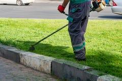 L'herbe de coupe de jardinier par la tondeuse ? gazon photo stock