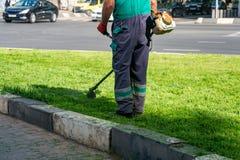 L'herbe de coupe de jardinier par la tondeuse ? gazon photographie stock