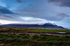 L'herbe verte avec la neige a couvert le durin islandais de paysage de montagnes Images libres de droits