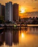 L'heure d'or avec des bâtiments a réfléchi sur l'eau d'un lac en parc Quelques personnes sur la plate-forme de parcs appréciant l Photographie stock libre de droits