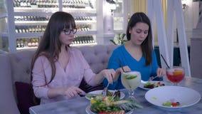 L'heure de manger, les amies appréciant le déjeuner délicieux pendant le régime et mange de la salade grecque des plats en café banque de vidéos