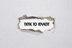 L'heure de mot d'inventer apparaître derrière le papier déchiré Photographie stock