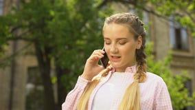L'heureuse femme enceinte parlant au téléphone après avoir rendu visite au gynécologue, genre indiquent banque de vidéos
