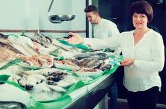 L'heureux achat d'homme et de femme a refroidi sur des poissons photo libre de droits
