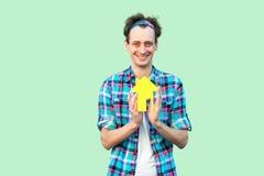 L'heureux jeune homme adulte optimiste positif gai dans la chemise à carreaux ont le rêve et tenir la petite maison de papier, pr images stock