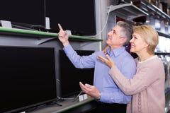 L'heureux mari et épouse choisissent pour eux-mêmes la TV au centre d'électr. Photo libre de droits