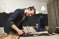 L'hispanique aux cheveux foncés attirant joyeux mûr, couturier masculin travaillant à la nouvelle robe dans l'atelier, coupant pa photos libres de droits