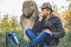L'historien instruit s'assied avant la sculpture en pierre sur le monticule images libres de droits
