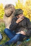 L'historien instruit s'assied avant la sculpture en pierre sur le monticule image libre de droits
