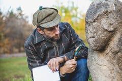 L'historien scientifique examine par la SCU de pierre de loupe images stock