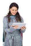 L'hiver de port de sourire de jolie brune vêtx tenir sa table Photos libres de droits