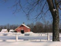 L'hiver : grange rouge avec l'arbre dans la neige Photo libre de droits