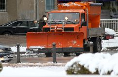 L'hiver Le chasse-neige nettoie la route dans la ville pendant une tempête de neige énorme, machine propre de neige sur le boulev image libre de droits