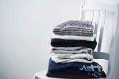 L'hiver vêtx sur la chaise sur un fond blanc de mur Images stock