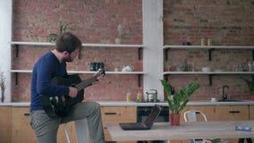 L'hobby musicale, tipo barbuto allegro del chitarrista che impara lo strumento musicale messo insieme gioco utilizza il computer  video d archivio