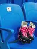 L'hockey noir patine avec des lacets de chaussures de cinglement sur la chaise sur le stade vide Photos libres de droits