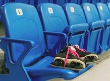 L'hockey noir patine avec des lacets de chaussures de cinglement sur la chaise sur le stade vide Les rangées ont une numération Photographie stock libre de droits