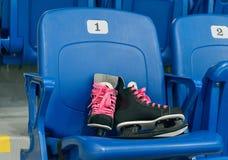 L'hockey noir patine avec des lacets de chaussures de cinglement sur la chaise sur le stade vide La chaise a un numéro un Photos libres de droits