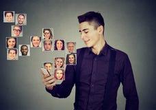 L'homme à l'aide du téléphone intelligent a beaucoup de contacts en annuaire téléphonique mobile Image stock