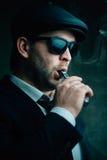 L'homme à la mode dans les lunettes de soleil et un chapeau en cuir fume Photo stock