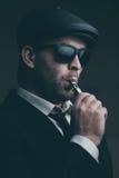 L'homme à la mode dans les lunettes de soleil et un chapeau en cuir fume Images stock
