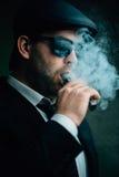 L'homme à la mode dans les lunettes de soleil et un chapeau en cuir fume Photos stock