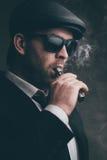 L'homme à la mode dans les lunettes de soleil et un chapeau en cuir fume Images libres de droits