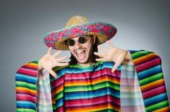 L'homme à un arrière-plan gris de poncho mexicain vif d'isolement Image stock