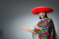 L'homme à un arrière-plan gris de poncho mexicain vif d'isolement Photographie stock libre de droits