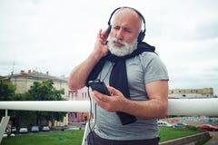 L'homme âgé élégant dans des écouteurs apprécie la musique du téléphone intelligent Photographie stock libre de droits