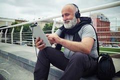 L'homme âgé élégant dans des écouteurs avec la tablette s'assied sur un SI Photos libres de droits