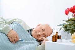 L'homme âgé par aîné se repose tout en tenant a Photo stock