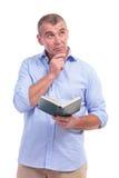 L'homme âgé par milieu occasionnel avec le livre, pense Images libres de droits