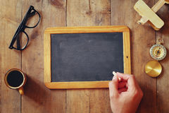 L'homme écrit sur un tableau noir vide sur la table en bois Image stock