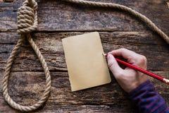 L'homme écrit une note de suicide Photographie stock libre de droits