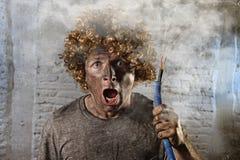 L'homme électrocuté avec le câble fumant après accident domestique avec le choc brûlé sale de visage a électrocuté l'expression Photographie stock