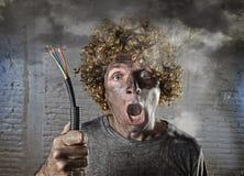 L'homme électrocuté avec le câble fumant après accident domestique avec le choc brûlé sale de visage a électrocuté l'expression Photos stock