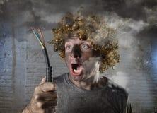 L'homme électrocuté avec le câble fumant après accident domestique avec le choc brûlé sale de visage a électrocuté l'expression Photos libres de droits