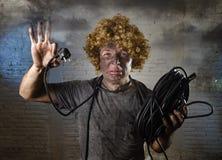 L'homme électrocuté avec le câble fumant après accident domestique avec le choc brûlé sale de visage a électrocuté l'expression Image stock