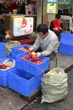 L'homme épluche des grenades en Chine Photographie stock libre de droits