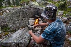 L'homme a établi un feu de camp dans les bois en nature Survivez dans les montagnes dans la forêt, faisant cuire dans une cassero images stock