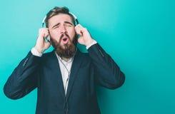 L'homme étonnant écoute la musique par de grands écouteurs Il est chantant et appréciant le moment D'isolement sur le bleu image stock