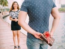 L'homme étonne son amie en donnant un cadeau - amour et rel Image stock