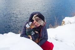 L'homme étreint le petit chien, portant dans un chapeau drôle d'hiver Photos libres de droits
