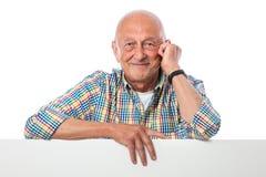 L'homme aîné de sourire heureux retient un panneau blanc Photographie stock libre de droits